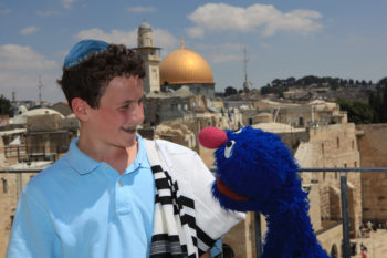"""Michael Rosenberg of New York City chats with Grover, who attended his bar mitzvah in Jerusalem as part of the """"Shalom Sesame"""" filming, on Aug. 28, 2009. (Koby Gideon / Flash 90)"""