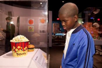 """Ihsan Abdussabur is looking at an exhibit that shows that a medium-sized container of movie popcorn has the same number of calories as four hamburgers and 12 pats of butter, the exhibit is part of the """"Big Food: Health, Culture and the Evolution of Eating,"""" exhibit at the Yale Peabody Museum of Natural History in New Haven, Conn.  (Yale School of Public Health)"""