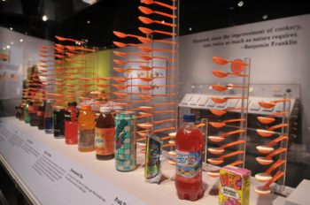 """The drink exhibit at the """"Big Food: Health, Culture and the Evolution of Eating,"""" exhibit at the Yale Peabody Museum of Natural History in New Haven, Conn., shows that Many popular beverages pack a sugary punch, with some having as many as 20 spoonfuls in a single container.  (Yale School of Public Health)"""
