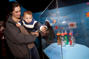 """Pablo Cruz and his mother, Sarah Miller, reacting to a display on the power of food marketing—logos from popular soft drink companies on baby bottles at the """"Big Food: Health, Culture and the Evolution of Eating,"""" exhibit at the Yale Peabody Museum of Natural History in New Haven, Conn. (Yale School of Public Health)"""
