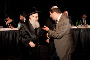 Rabbi Asher Lopatin, right, the incoming president of the Modern Orthodox Yeshivat Chovevei Torah, confers with Rabbi Yehoshua Eichenstein, the Zidichiver rebbe, at Chicago's Siyum HaShas celebration on Aug. 1, 2012. Lopatin says he wants to expose Chovevei's rabbinical students to a broader array of Orthodox viewpoints.  (Fred Eckhouse Photography)