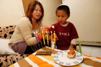 Filipinos light Chanukah candles in their home in South Tel Aviv on Nov. 24, 2010 in advance of the Jewish holiday.  (Miriam Alster/FLASH90)