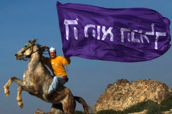"A settler rides his horse in Havat Gilad while holding a flag that says ""God is the King."" (Nati Shohat / Flash 90/JTA)"