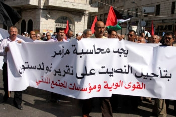 Palestinian demonstrators raise flags and chant slogans during an Oct. 5, 2009 demonstration in Ramallah against Palestinian Authority President Mahmoud Abbas' decision to delay sending the Goldstone Commission report to the U.N. Security Council. (Issam Rimawi / Flash 90 / JTA)