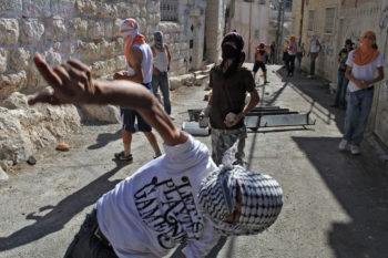 Arab youths hurl stones at Israeli border policemen in the eastern Jerusalem neighborhood of Ras al-Amud on Oct. 6, 2009.  (Nati Shohat / Flash 90 / JTA)