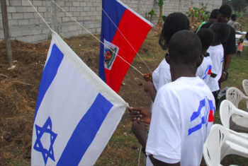 Children raise the Israeli and Haitian flags as the national anthems of both countries are played during a ceremony at a refugee camp on the edge of Port-au-Prince, March 2010. (Larry Luxner)