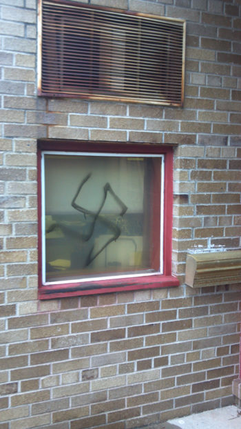 A swastika spray-painted on a window of Temple Beth El in Hackensack, N.J., Dec. 10, 2011. (ADL)