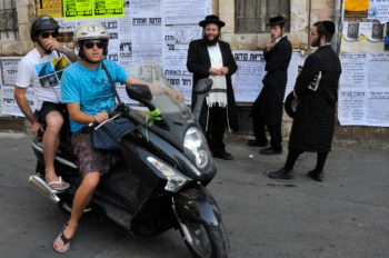 Israelis on a motorcycle piquing the interest of haredi Orthodox Jews in the haredi Jerusalem neighborhood of Mea Shearim.  (Serge Attai/Flash90)