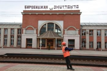 A railway worker conducts repairs to the Birobidzhan railway station. The sign behind him is in both Russian and Yiddish. (Grant Slater)