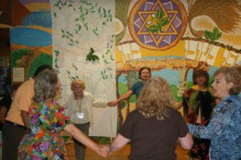 Participants at the Isabella Freedman Senior Camp in Falls Village, Conn., dancing next to the tree mural they created, with notes expressing the accomplishments in which they take the most pride and their hopes serving as the leaves.  (Courtesy Isabella Freedman Jewish Retreat Center)
