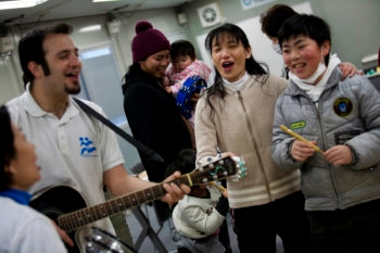 Yotam Polizer, IsraAID's Japan project manager, plays the guitar for residents of a temporary housing site for tsunami survivors in Ishinomaki as part of a music therapy session run by post-trauma experts from the Israeli NGO. Community leader Chiho Shimura, center, is among those enjoying Polizer's music. (Boaz Arad)