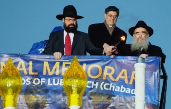 """Jack Lew, center, helps light the """"national menorah"""" organized by American Friends of Lubavitch, with the group's director, Rabbi Levi Shemtov, left, and his father, Rabbi Abraham Shemtov, the director of Agudas Chasidei Chabad, Dec. 20, 2011. (Baruch Ezagui, courtesy of American Friends of Lubavitch.)"""