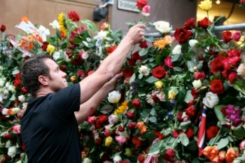 During  the 100,000-person Rose March, a man places a flower into the fence separating downtown Oslo from the exclusion zone set up by Norwegian police around the blast site, July 25, 2011. (Alex Weisler)