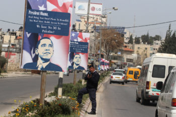 A Palestinian policeman in the West Bank city of Ramallah standing next to a poster with a slogan protesting the upcoming visit of President Obama, March 12, 2013.  (Issam Rimawi/FLASH90)