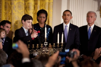 Ben Retik lights the Menorah as President Barack Obama, Vice President Joe Biden and First Lady Michelle Obama take part in the Hanukkah Candle Lighting ceremony in the East Room of the White House,Dec. 2, 2010. (Official White House Photo by Chuck Kennedy)