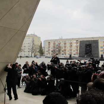 Poland's chief rabbi, Michael Schudrich, unveiling the mezuzah on the entrance to the Museum of the History of Polish Jews in April 2013. In the background, the monument to the Ghetto Heroes, erected in 1948. (Ruth Ellen Gruber)