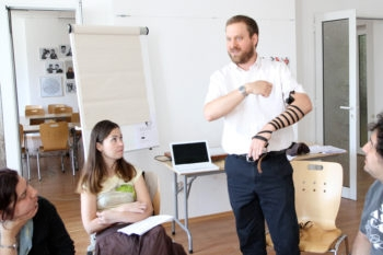 Rabbi Josh Ahrens demonstrating how to put on tefillin during a conversion course at the Sofia JCC in Bulgaria, May 6, 2012.  (Dianna Cahn)