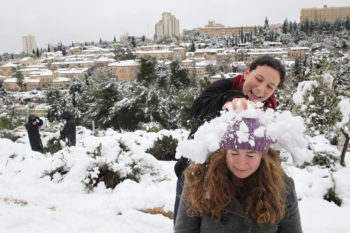 Young Israelis playing in the snow, with the snowy Jerusalem neighborhood Mishkenot Sha'ananim in the background, Jan. 10, 2013. (/JTA)  (Nati Shohat/Flash90)