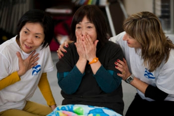 Kohata Yuriko, who saved her father and her son from the tsunami, is comforted by IsraAID project coordinator/translator Celia Dunkelman, left, and therapist Osnat Nisanov, right, at a workshop in one of Iwanuma's many temporary housing sites.  (Boaz Arad)