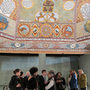 Visitors standing under the painted reconstruction of the ceiling of the Gwozdziec synagogue. (Ruth Ellen Gruber)