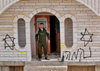 A Palestinian man stands at the entrance to his home defaced with Magen Davids and the word revenge on Dec. 4, 2008 near the house from which settlers were evicted.  (Brian Hendler)