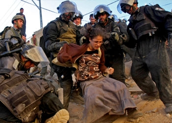 Israeli police take away a protester during evacuation of a controversial Hebron home on Dec. 4, 2008. (Brian Hendler)