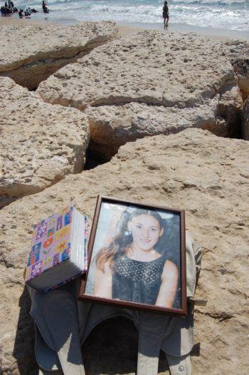 A framed photograph of Yevgenia Dorfman, 15, who was killed in a suicide bombing at the Tel Aviv's seaside Dolphinarium disco, rests on a rock along the beach just south of where the attack took place 10 years ago. (Dina Kraft)