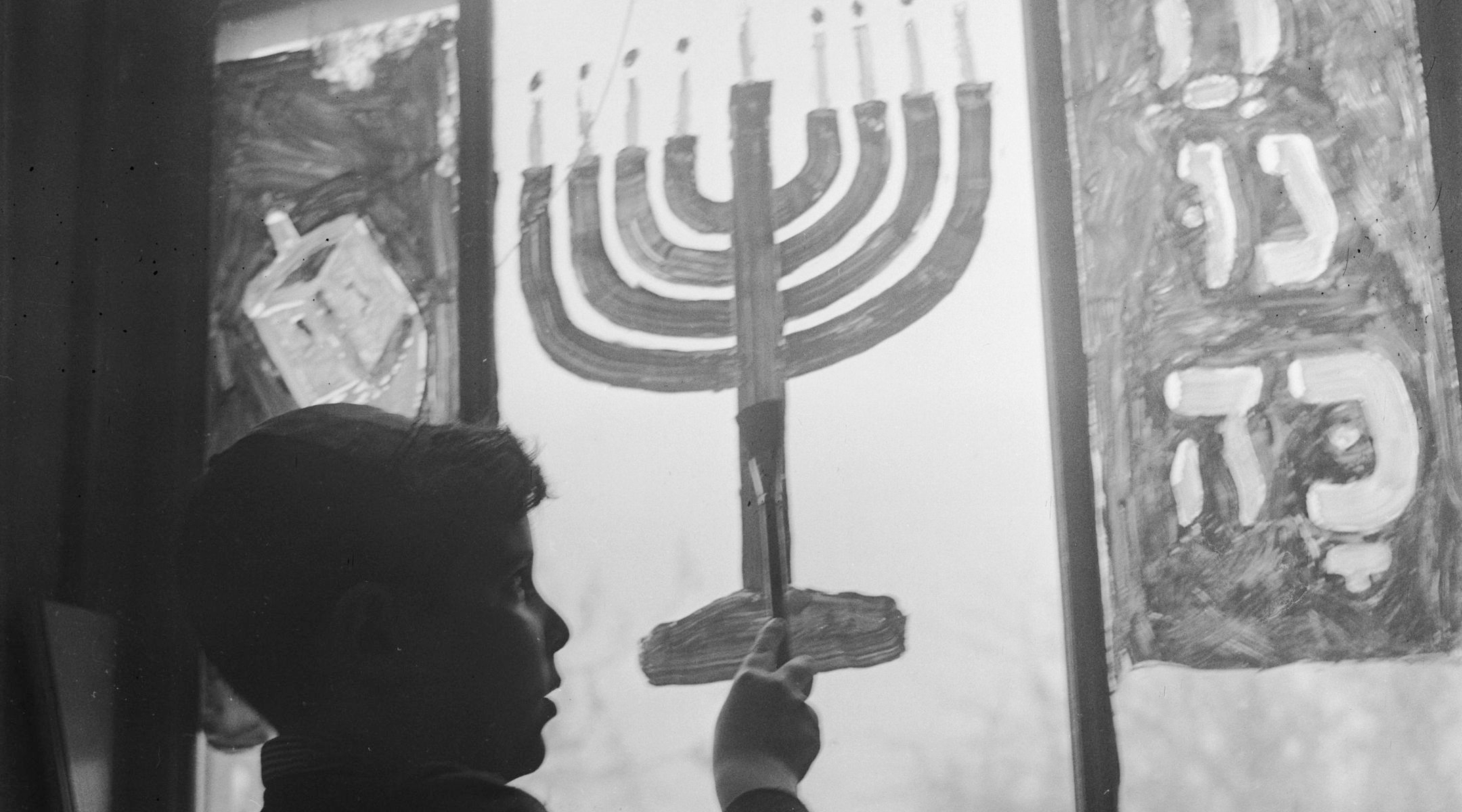 boy painting menorah